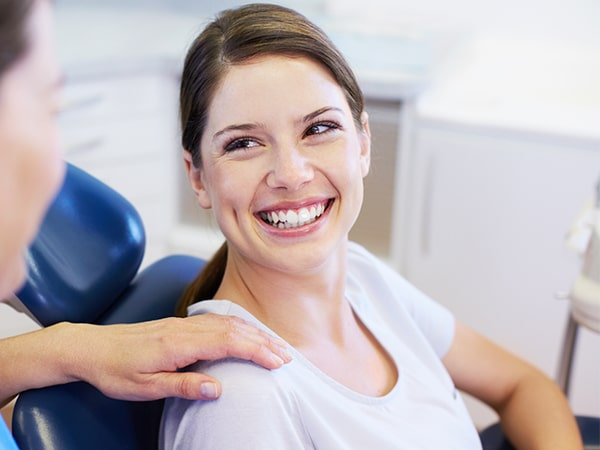 A young woman sitting in the dentist's chair smiling